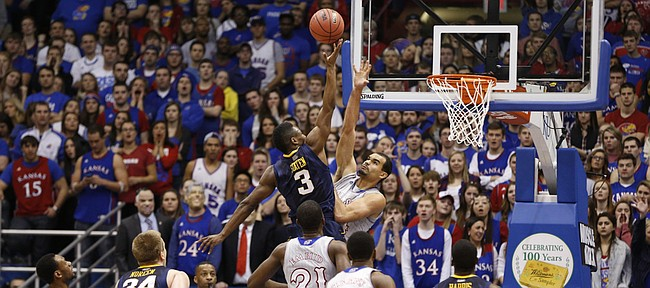 Kansas forward Perry Ellis defends as West Virginia guard Juwan Staten puts up a shot during the first half on Saturday, Feb. 8, 2014 at Allen Fieldhouse.