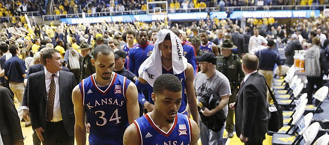 Kansas guard Frank Mason III (0), Perry Ellis (34) and Landen Lucas, background right, walk off the court as West Virginia fans storm the court after defeating the Jayhawks 62-61 Monday, February 16, 2105  in Morgantown, W.V.