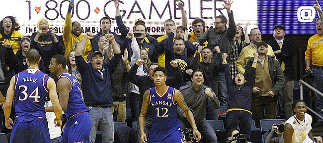 Kansas guard Kelly Oubre, Jr. looks to the scoreboard clock as the Mountaineers crowd celebrates a late game basket by West Virginia guard Juwan Staten (3), far right. Staten's shot was the deciding basket in the Jayhawks 62-61 loss to the Mountaineers Monday, February 16, 2105  in Morgantown, W.V.