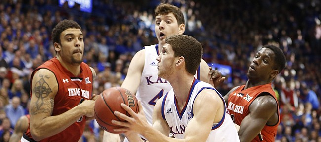 Kansas guard Sviatoslav Mykhailiuk (10) gets to the bucket past Texas Tech forward Justin Jamison (4) and guard Devaughntah Williams during the second half on Saturday, Jan.10, 2015 at Allen Fieldhouse. Also pictured is Kansas forward Hunter Mickelson.