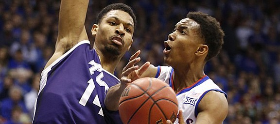 Kansas guard Devonte Graham (4) gets to the bucket against TCU center Karviar Shepherd (14) during the first half, Saturday, Feb. 21, 2015 at Allen Fieldhouse. At right is Kansas forward Jamari Traylor.