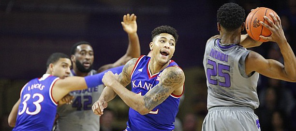 Kansas guard Kelly Oubre Jr. (12) takes a swipe at a ball held by Kansas State forward Wesley Iwundu (25) during the first half, Monday, Feb. 23, 2015 at Bramlage Coliseum.