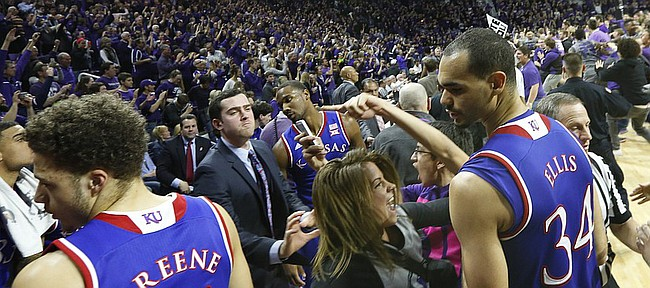 Kansas forward Perry Ellis and Kansas guard Brannen Greene try to move to the sidelines as Kansas State fans rush the court following the Jayhawks' 70-63 loss to the Wildcats, Monday, Feb. 23, 2015 at Bramlage Coliseum.