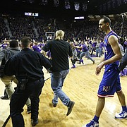 Journal-World photographer Nick Krug has learned a thing or two about how to prepare and navigate a court-storming, such as this one when Kansas State fans rushed the court at Bramlage Coliseum on Feb. 23 after the Wildcats defeated the Jayhawks. At right, a fan runs into KU's Jamari Traylor, which caused a national discussion about the safety risks posed by court-storming.
