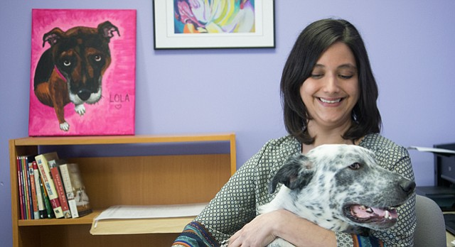 Kate Meghji, executive director at the Lawrence Humane Society, holds one of the shelter's dogs up for adoption in this March 2015 file photo.