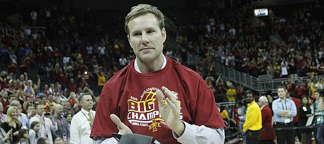 Iowa State coach Fred Hoiberg holds a championship hat and claps for his Cyclones after winning the Big 12  Tournament on Saturday, March 14, 2015. ISU beat Kansas 70-66 in Kansas City, Missouri.