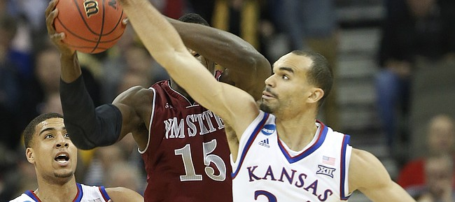 Kansas forward Perry Ellis (34) looks to make a steal on New Mexico State center Tshilidzi Nephawe (15)in the Jayhawks 75-56 win against New Mexico State Friday, March 20, 2015 at the CenturyLink Center, Omaha, NE..