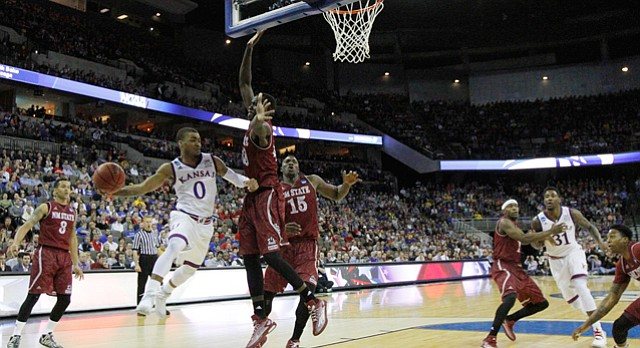 Kansas guard Frank Mason III (0) passes beneath the basket in the Jayhawks second-round NCAA tournament game against New Mexico State Friday, March 20, 2015 at the CenturyLink Center, Omaha, Neb. .