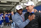 Kansas head football coach David Beaty and Je'Ney Jackson, director of strength and conditioning have a laugh as the team waits under the Memorial Stadium stands as a lightning storm passes during spring practice on Tuesday, March 24, 2015.