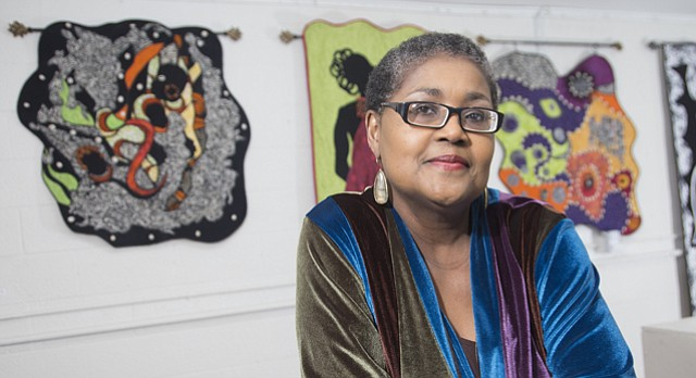 """Quilter and historian Marla Jackson is pictured in front of her quilts on display at the Percolator, 913 Rhode Island St., as part of Jackson's upcoming exhibition, """"Tell Mama."""" The exhibit, which opens during this month's Final Friday, features 10 quilts that honor her mother, Fern Hill."""