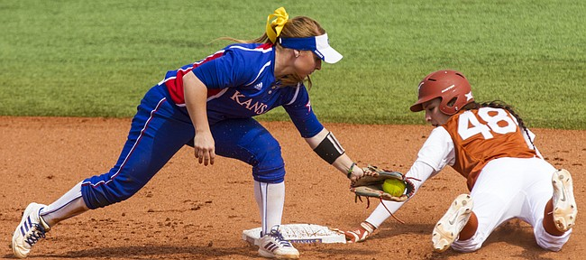 Texas junior Stephanie Ceo (48) looks back at the bag after stealing second base and beating a tag by Kansas junior Chaley Brickey during their game Sunday afternoon at Arrocha Ballpark.