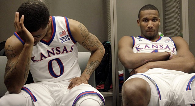 Frank Mason III, left and Wayne Selden Jr. sit at their lockers after the Jayhawks' 78-65 loss to Wichita State Sunday, March 22, 2015 at the CenturyLink Center, Omaha, Neb. Expanding the view from the previous frame of Frank Mason III by himself, a viewer gains a slightly different perspective. I felt that having both players included added more context and additional impact.