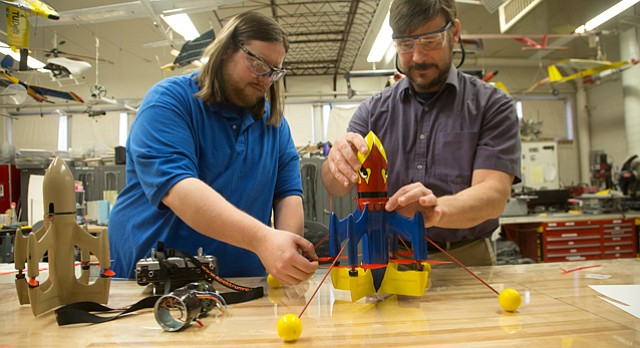 "KU mechanical engineering doctoral student Richard Bramlette, left, and associate professor of aerospace engineering Ron Barrett-Gonzalez prepare to fly a drone they developed inside an aerospace lab at Learned Hall. The patent-pending XQ139A drone, nicknamed ""Robby"" and painted like a Jayhawk, was designed to be flown for fun. A similar B model envisioned for police and military use is not yet ready to debut, they said."