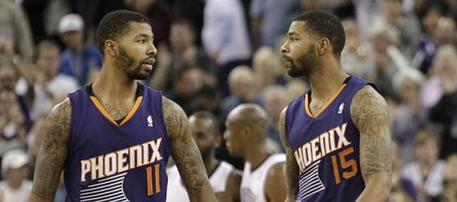 Phoenix Suns' Markieff Morris, left, shakes hands with his twin brother Marcus, as they walk off the court after the Suns 107-104 loss to the Sacramento King in a NBA basketball game in Sacramento, Calif., Tuesday, Nov. 19, 2013.(AP Photo/Rich Pedroncelli)