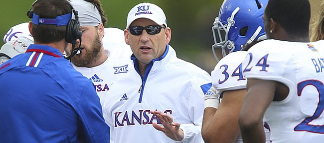 Kansas head coach David Beaty talks with his players after starting quarterback Michael Cummings left the game with an injury during the Spring Game on Saturday, April 25, 2015 at Memorial Stadium.