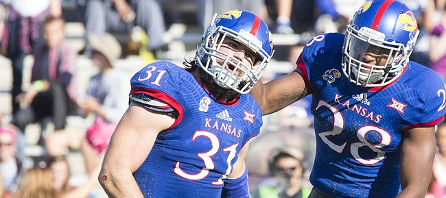Kansas senior linebacker Ben Heeney (31) and sophomore lineback Courtney Arnick celebrate Heeney's quarterback sack during their game against Oklahoma State Saturday at Memorial Stadium.