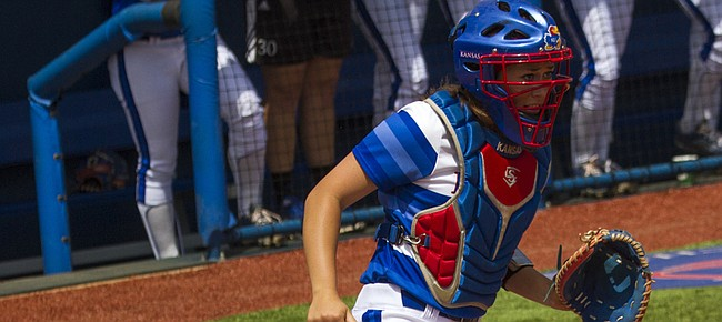 Baylor sophomore Lindsey Cargill slides safely into home behind Kansas freshman catcher Jessie Roane during the Jayhawks' game against Baylor Sunday at Arrocha Ballpark.