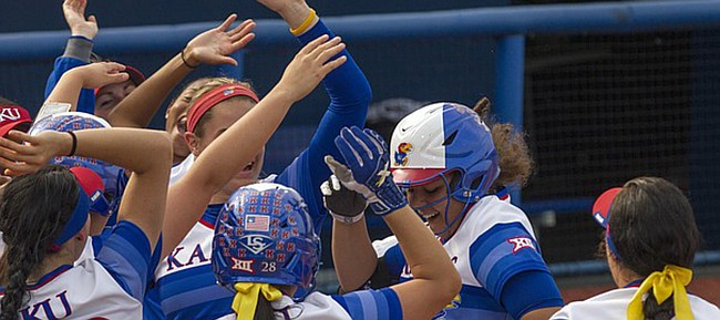 Kansas freshman Daniella Chavez is met by her teammates at home plate after drilling a two-run home run over the right field wall during the Jayhawks' game against Baylor Friday evening at Arrocha Ballpark.