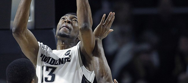 Providence center Paschal Chukwu (13) goes up for a shot against Marquette guard Derrick Wilson during the first half of a game, Sunday, March 1, 2015, in Providence, Rhode Island.
