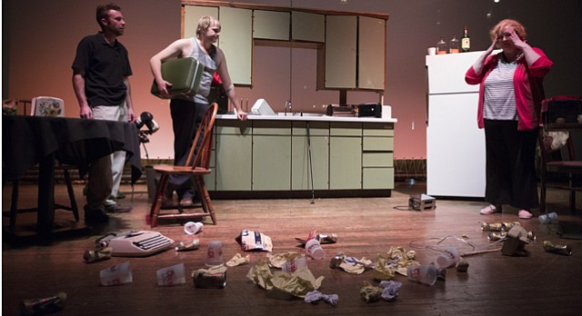 "Mom, played by Maggie Allen, pulls her hands to her head as she comes to witness her kitchen trashed with beer cans and other messes created by her sons Austin, left, and Lee, played by Chris Roady and Derek Trautwein, during a dress rehearsal for Sam Shepard's ""True West"" on Tuesday, June 2, 2015, at Liberty Hall."