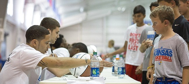 SMU's Nic Moore signs autographs for fans during the registration for Bill Self's basketball camp Sunday at Anschutz Sports Pavilion.