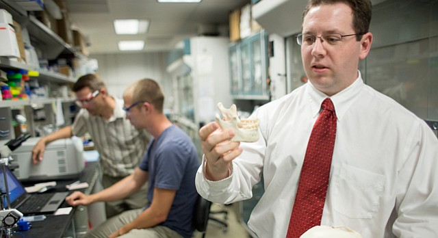 Michael Detamore, director of the biomaterials and tissue Engineering Laboratory at KU, describes how 3-D printing technology is being researched at KU in tissue engineering efforts focused mainly on bone and cartilage regeneration. In background working with a 3D printer at left is Stefan Lohfeld, Marie Curie Visiting Scientist at KU, and incoming freshman Mason Wilde, Louisburg.