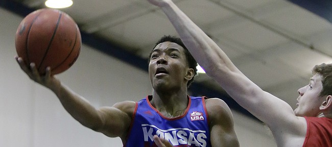 Kansas guard Devonté Graham slides past center Hunter Mickelson during a practice game between current and former KU players Wednesday, June 17, 2015 at a Bill Self Basketball Camp.