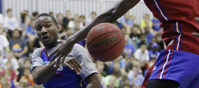 Kansas guard Wayne Selden Jr., left, passes beneath the basket and the defense of Carlton Bragg during a practice game between current and former KU players Wednesday, June 17, 2015 at a Bill Self Basketball Camp.