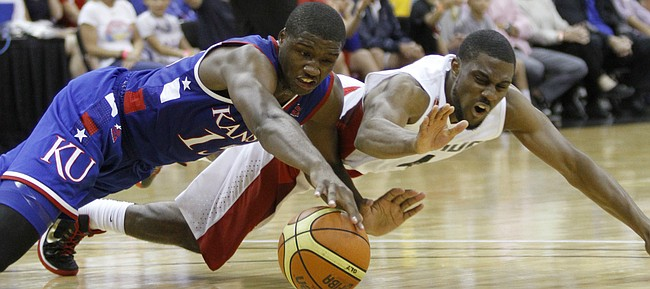 Kansas forward Carlton Bragg, left, hits the floor for a loose ball with Canada guard Jarred Ogungbemi-Jackson in the first-half of a Team USA exhibition game against Canada Tuesday, June 23, at the Sprint Center in K.C., MO.