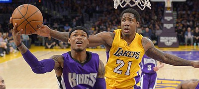 Sacramento Kings guard Ben McLemore, left, goes up for a shot as Los Angeles Lakers forward Ed Davis, center, defends and forward Carl Landry watches during the first half of an NBA basketball game Wednesday, April 15, 2015, in Los Angeles. (AP Photo/Mark J. Terrill)