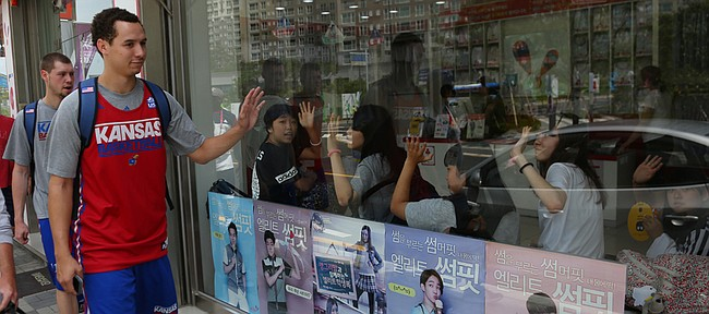 Tyler Self, left and Evan Manning pass by diners in an ice cream shop in Gwangju as Team USA walks from Athletes Village to a nearby high school for an outdoor practice Friday, July 3.