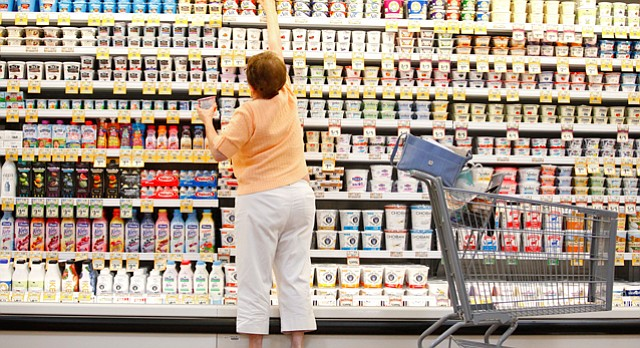 "Lawrence resident Sandy Warnock reaches for the top-shelf yogurt as she makes her way through the dairy section on Tuesday, June 30, 2015 at Sprouts Farmers Market, 4740 Bauer Farm Drive. ""I'm tickled to death that they are here,"" said Warnock. The new grocer invited handfuls of local residents to get a first look at the store before Wednesday's grand opening."