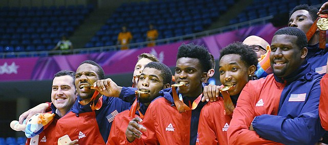 Team USA players bite on their gold medals after a win against Germany Monday, July 13, at the World University Games in South Korea.