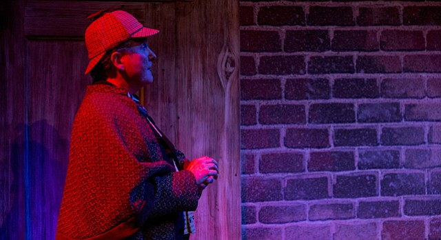 "Sherlock Holmes, portrayed by Robert Brand and wearing Holmes' classic deerstalker hat, inspects a building during a dress rehearsal for the upcoming Kansas Repertory Theatre production of ""Sherlock's Last Case"" on Tuesday evening at Crafton-Preyer Theatre in Murphy Hall. The show opens on Friday and runs through early August concurrently with a production of Agatha Christie's ""The Mousetrap."""
