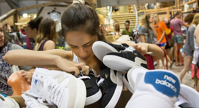Lauren Brittain, of Lawrence, looks through some shoes at Urban Outfitters, 1013 Massachusetts St., during the 56th annual Downtown Lawrence Sidewalk Sale, Thursday, July 16, 2015.