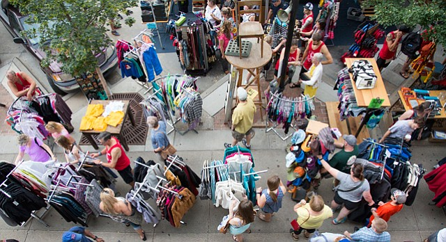 Shoppers check out the deals at Sunflower Outdoor and Bike Shop, 804 Massachusetts St., during the Downtown Lawrence Sidewalk Sale, Thursday, July 16, 2015.