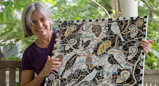 Lawrence artist and community arts educator Lora Jost has created several public art projects in Lawrence and continues to create theme-based mixed-media pieces. Jost holds a mosaic from her series Sound the Climate Alarm.