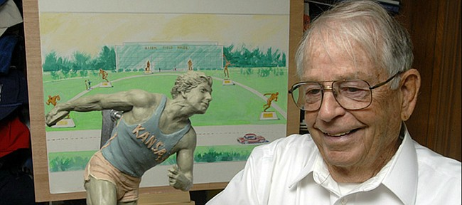 In this file photo from 2006, former Kansas University track coach Bob Timmons talks about an idea for a walk of fame of KU greats leading up to Allen Fieldhouse. A small model of a statue of Al Oerter, a famous track star at KU and Olympic recordholder, sits on Timmons' desk at his home.