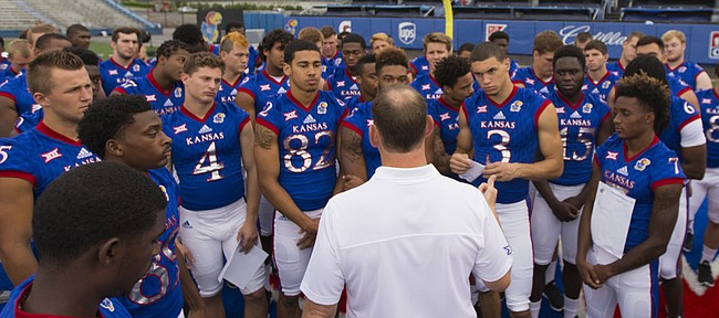Head coach David Beaty talks with his team prior to a round of portraits with media members on Saturday, Aug. 8, 2015 at Memorial Stadium.