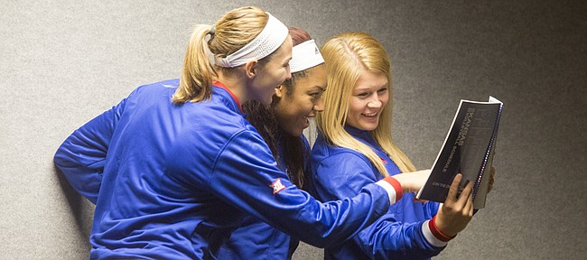 Kansas University volleyball players, from left, Tayler Soucie, Tiana Dockery and Cassie Wait make fun of their pictures in the media guide during KU fall sports media day Wednesday, Aug. 19, 2015, at Hadl Auditorium.