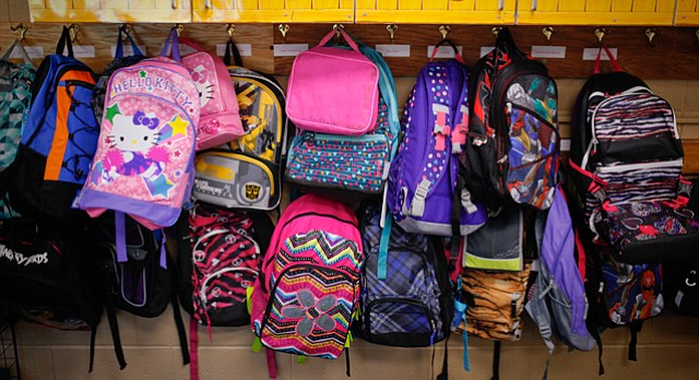 Bookbags crowd together on hooks in a second-grade classroom on the first day of school for Lawrence elementary schools in this file photo from Aug. 13, 2014.