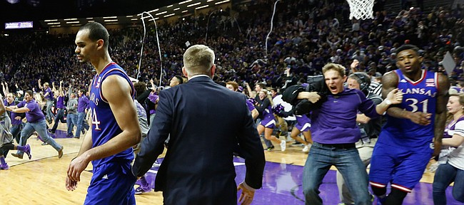 Kansas forward Perry Ellis moves to the sideline as fans rush the court following the Jayhawks' 70-63 loss to the Wildcats, Monday, Feb. 23, 2015 at Bramlage Coliseum. At right, a Kansas State fan bumps into Kansas forward Jamari Traylor.
