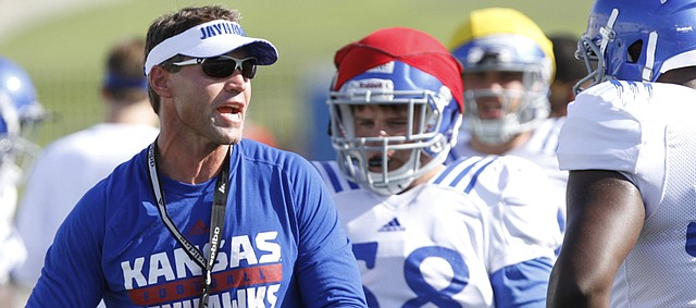 Kansas assistant head coach and defensive coordinator Clint Bowen instructs players at a KU football practice that was part of fan appreciation activities Saturday August 8, 2015.