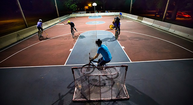 A player reaches back to swing as a defender blocks the net during a bike polo game on Thursday, Aug. 13, 2015 at Edgewood Park in East Lawrence. Members of the Scary Larry club say that they have been well-received by the neighborhood and by those who feel safer in the park at night with regular activity going on.