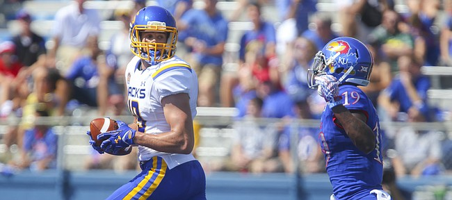 South Dakota State wide receiver Jake Wieneke (19) turns back to see Kansas cornerback Tyrone Miller Jr. (19) trailing as he runs into the end zone for a touchdown during the first quarter on Saturday, Sept. 5, 2015 at Memorial Stadium.