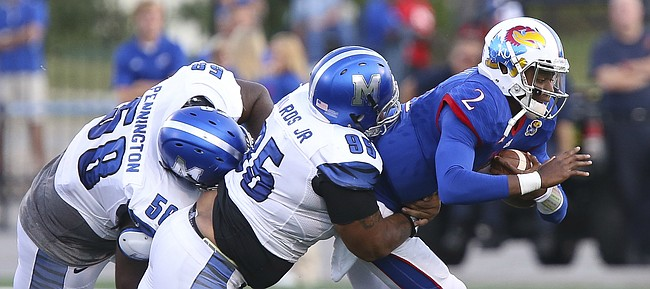 Kansas quarterback Montell Cozart (2) is dragged down in the backfield by Memphis defensive lineman Donald Pennington (58) and defensive lineman Michael Edwards (95) during the second quarter on Saturday, Sept. 12, 2015 at Memorial Stadium.