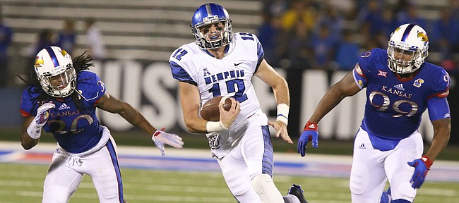Memphis quarterback Paxton Lynch (12) escapes Kansas defenders Tevin Shaw (30) and Corey King (99) during the third quarter on Saturday, Sept. 12, 2015 at Memorial Stadium.