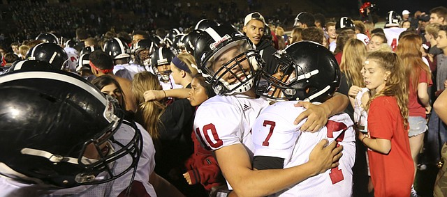 Lawrence High quarterback Alan Clothier (7) is hugged by teammates after the Lions' 14-12 win over Free State on Friday, Sept. 17, 2015 at Free State High School.
