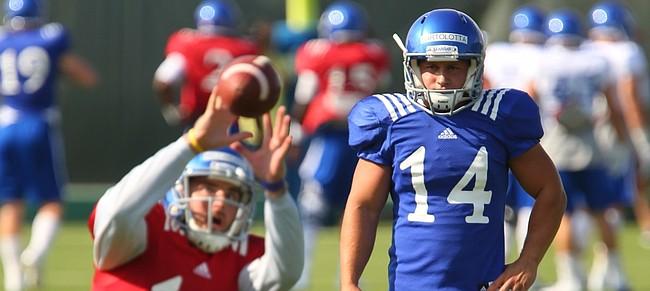 Kansas kicker Nick Bartolotta (14) watches as T.J. Millweard takes the snap during practice on Monday, Aug. 10, 2015.