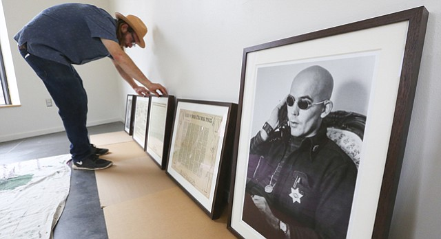 "Lawrence native D.J. Watkins, founder of the Gonzo Gallery in Aspen, Colo., and author of ""Freak Power,"" organizes framed pieces of memorabilia from famed journalist Hunter S. Thompson's run for sheriff of Pitkin County, Colo., Monday, Sept. 21, 2015 at the Lawrence Arts Center. The show opens Sept. 25."